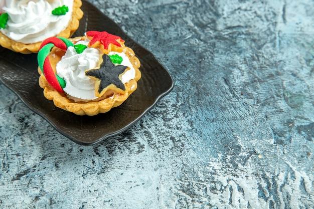 Onderaanzicht kleine kersttaartjes op grijze tafel met vrije ruimte