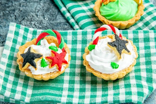 Onderaanzicht kleine kersttaartjes op groen tafelkleed op grijze tafel
