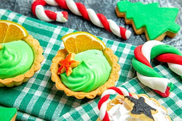 Onderaanzicht kleine kersttaartjes op tafelkleed kerstboomkoekje op grijze tafel
