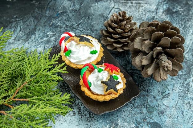 Onderaanzicht kleine kersttaartjes op zwarte plaat dennenappels dennentakken op grijze tafel