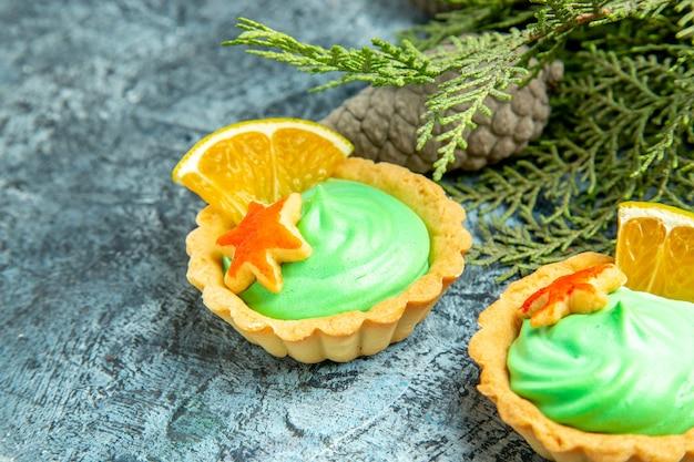 Onderaanzicht kleine taart met groene banketbakkersroom dennenappels op grijs oppervlak