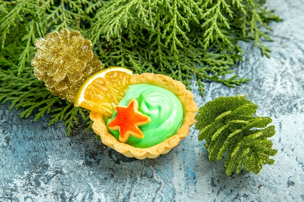 Onderaanzicht kleine taart met groene banketbakkersroom dennentakken mas ornamenten op grijs oppervlak
