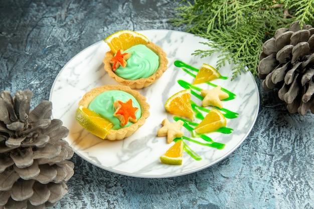 Onderaanzicht kleine taartjes met groene banketbakkersroom en schijfje citroen op plaat dennenappels op donkere ondergrond on