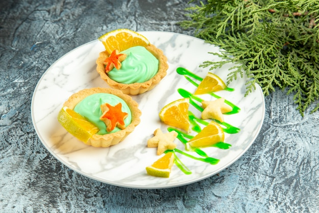 Onderaanzicht kleine taartjes met groene banketbakkersroom en schijfje citroen op plaat dennentak op donkere ondergrond