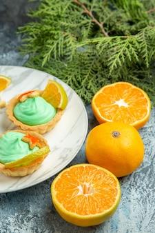 Onderaanzicht kleine taartjes met groene banketbakkersroom en schijfjes citroen op bord gesneden sinaasappels op donkere ondergrond