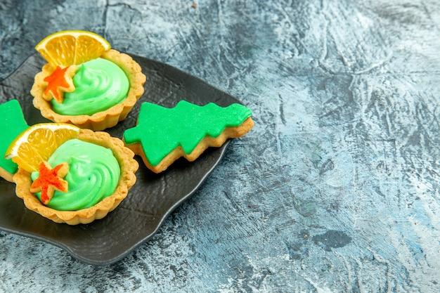 Onderaanzicht kleine taartjes met groene banketbakkersroom kerstboomkoekjes op zwarte plaat op grijs oppervlak met kopieerruimte