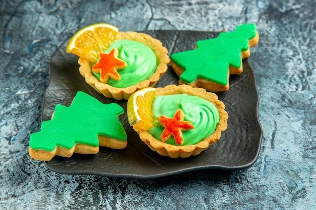 Onderaanzicht kleine taartjes met groene banketbakkersroom kerstboomkoekjes op zwarte plaat op grijs oppervlak