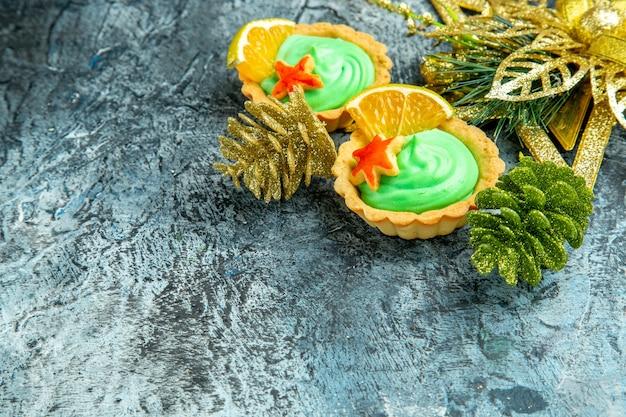Onderaanzicht kleine taartjes met groene banketbakkersroom kerstversieringen op grijs oppervlak met kopieerruimte