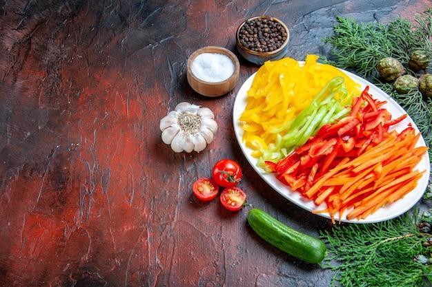 Onderaanzicht kleurrijke gesneden paprika's op plaat zout en zwarte peper tomaten knoflook komkommer op donkerrode tafel vrije ruimte