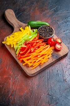 Onderaanzicht kleurrijke gesneden paprika's zwarte peper tomaten komkommer op snijplank op donkerrode tafel