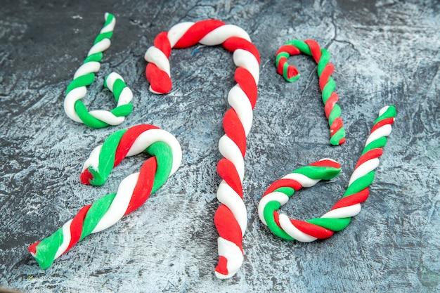 Onderaanzicht kleurrijke kerst snoepjes op grijze achtergrond