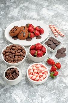 Onderaanzicht koekjes aardbeien en ronde chocolaatjes op de witte ovale schaal kommen met snoepjes aardbeien chocolaatjes granen op de grijs-witte tafel