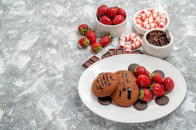 Onderaanzicht koekjes aardbeien en ronde chocolaatjes op de witte plaat en kommen met snoep aardbeien chocolaatjes op de grijs-witte ondergrond