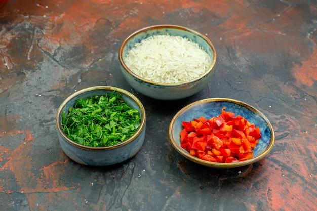 Onderaanzicht kommen met gehakte paprika's en groene rijst op donkerrode tafel
