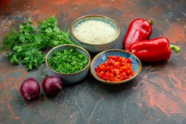 Onderaanzicht kommen met gehakte rode paprika's en groenten, rijst, peterselie, rode uien, rode paprika's op donkerrode tafel