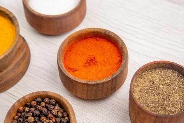 Onderaanzicht kommen met kruiden kurkuma peper poeder zout zwarte peper op tafel