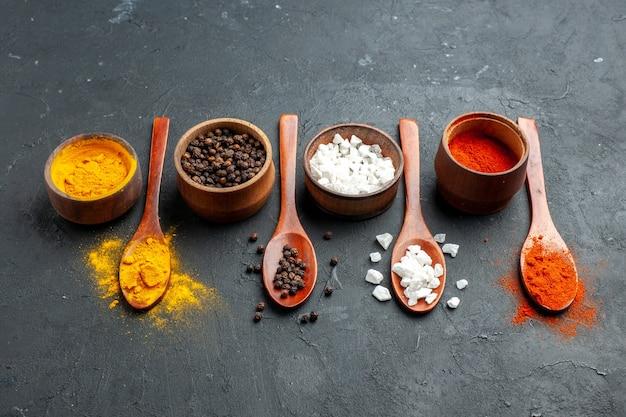 Onderaanzicht kommen met kurkuma zwarte peper sae zout rode peper poeder houten lepels op zwarte ondergrond