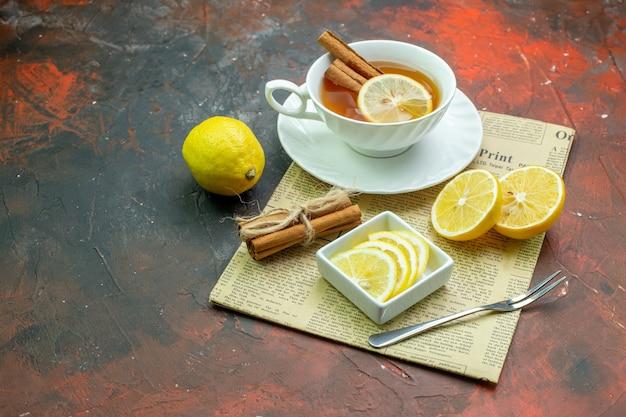 Onderaanzicht kopje thee met kaneel citroen schijfjes in kleine kom vork kaneelstokjes vastgebonden met touw op krant op donkerrode tafel vrije ruimte