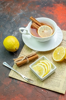 Onderaanzicht kopje thee met kaneel citroenschijfjes in kleine kom vork kaneelstokjes vastgebonden met touw op krant op donkerrode tafel