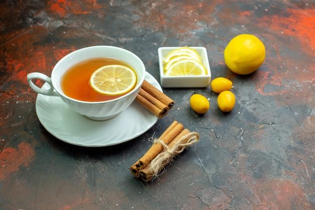 Onderaanzicht kopje thee op smaak gebracht door citroen cumcuat citroenschijfjes in kleine kom kaneel op donkerrode tafel