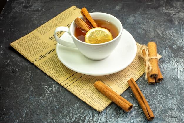 Onderaanzicht kopje thee op smaak gebracht door citroen en kaneel op krantenkaneelstokjes op donkere tafel