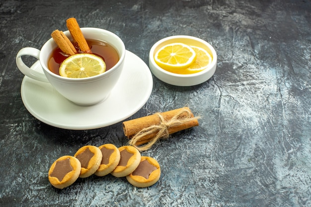 Onderaanzicht kopje thee op smaak gebracht met citroen en kaneel citroenschijfjes in kleine schotelkoekjes gebonden kaneelstokjes op donkere tafel vrije ruimte