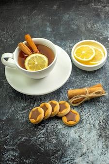 Onderaanzicht kopje thee op smaak gebracht met citroen en kaneel citroenschijfjes in kleine schotelkoekjes gebonden kaneelstokjes op donkere tafel