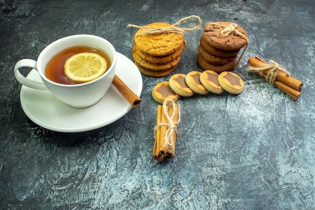 Onderaanzicht kopje thee op smaak gebracht met citroen en kaneel koekjes, koekjes vastgebonden met touw kaneelstokjes op grijze tafel vrije ruimte