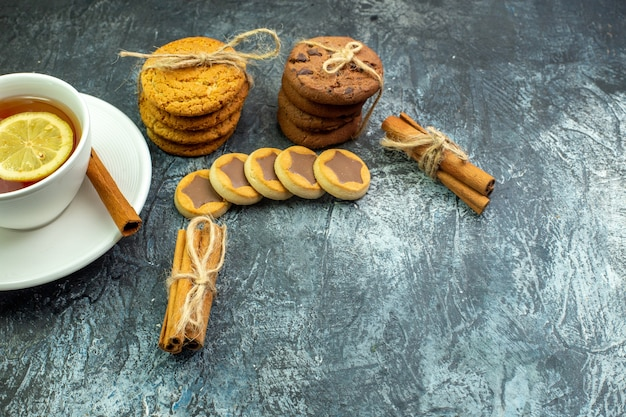 Onderaanzicht kopje thee op smaak gebracht met citroen en kaneelkoekjes, koekjes vastgebonden met touw kaneelstokjes op grijze tafel met vrije ruimte