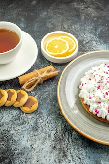Onderaanzicht kopje thee op smaak gebracht met kaneel citroenschijfjes in kleine schotel koekjes kaneelstokjes op donkere grond