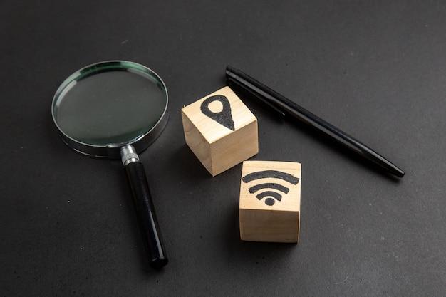 Onderaanzicht locatie en wifi-pictogrammen op houtblokken pen lupa op zwarte tafel