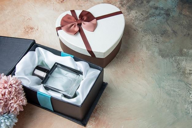 Onderaanzicht mannen cologne in doos hartvormige doos bloemen op tafel