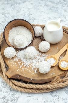 Onderaanzicht melkkom kokospoeder kom houten lepels kokosballen op een houten bord op grijze achtergrond
