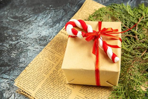 Onderaanzicht mini cadeau gebonden met rood lint kerstsnoep op krant op grijs