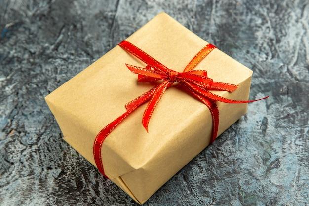 Onderaanzicht mini cadeau gebonden met rood lint op donkere geïsoleerde achtergrond
