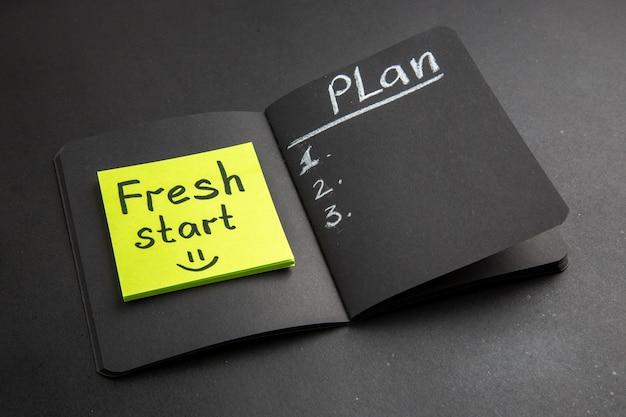 Onderaanzicht nieuwe start geschreven op notitieplan geschreven op zwart notitieblok op zwarte achtergrond