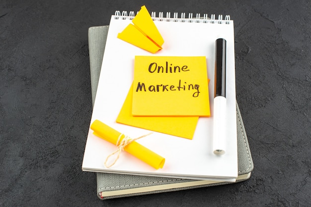 Onderaanzicht online marketing geschreven op gele plaknotitie zwarte stift op notitieblok op donkere achtergrond