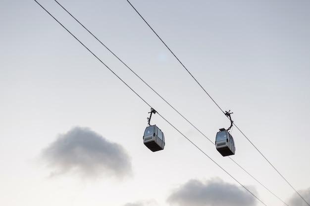 Onderaanzicht op moderne twee kabelbanen in de lucht met wolken in de avondtijd.