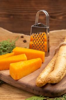 Onderaanzicht plakjes kaas broodrasp op snijplank pijnboomtakken op houten tafel