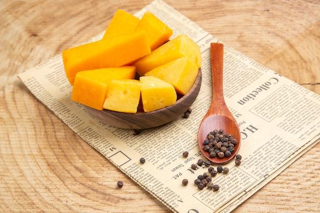 Onderaanzicht plakjes kaas in houten kom zwarte peper in houten lepel op krant op houten tafel