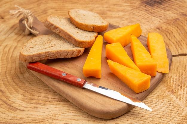 Onderaanzicht plakjes kaas sneetjes broodmes op snijplank op houten tafel