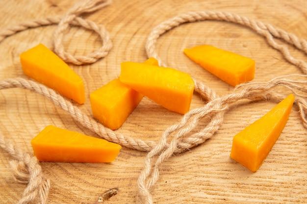 Onderaanzicht plakjes kaas touw op houten tafel