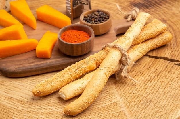 Onderaanzicht plakjes kaasdoos rasp kruiden op snijplank mes sneetjes brood op houten grond
