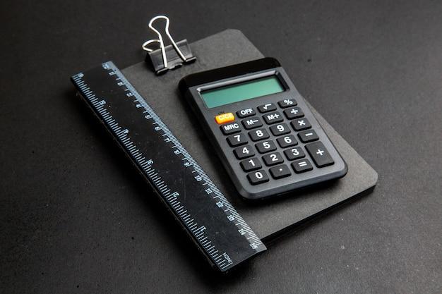 Onderaanzicht rekenmachine en liniaal op notitieblok op donkere tafel