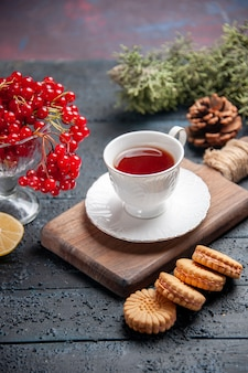 Onderaanzicht rode bes in een glas een kopje thee op een snijplank schijfje citroen dennenappels en koekjes op donkere houten achtergrond
