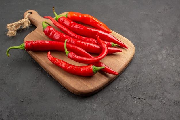 Onderaanzicht rode hete pepers op een diagonale snijplank op de zwarte tafel