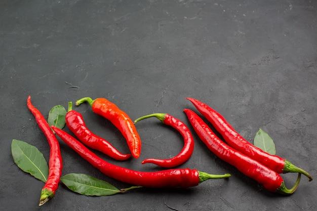Onderaanzicht rode paprika's en bladeren op zwarte achtergrond