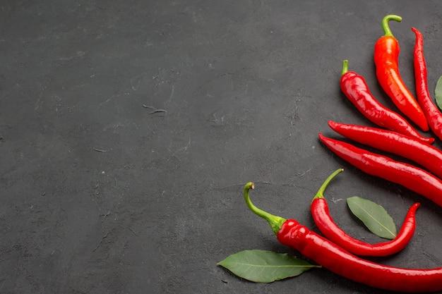 Onderaanzicht rode paprika's en loonblaadjes aan de rechterkant van de zwarte tafel