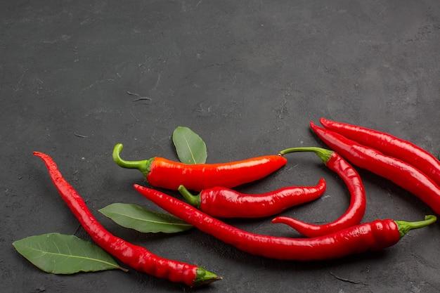 Onderaanzicht rode paprika's en loonblaadjes onderaan zwarte achtergrond
