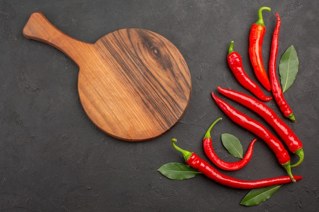 Onderaanzicht rode paprika's en loonbladeren en een snijplank op zwarte tafel